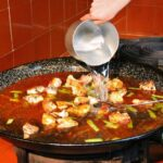Echando el agua en la paella valenciana