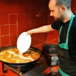 Echando el arroz en la paella valenciana