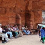 Turistas descansando ante el Tesoro de Petra en Jordania