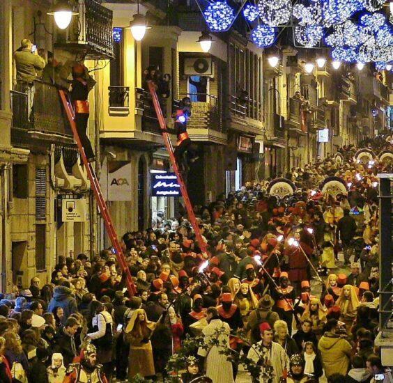 Pajes subiendo regalos en la Cabalgata de Reyes Magos en Alcoy